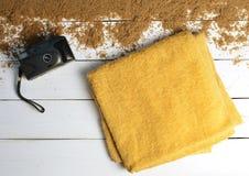 白色木表面上的一台海滩毛巾和葡萄酒照相机 放松的概念海上 夏天海滩季节是开放的!顶视图 库存照片