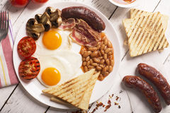 白色木表面上的英式早餐 免版税库存照片