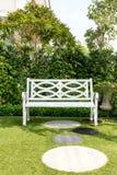 白色木长凳椅子有灌木背景在庭院里在家 图库摄影