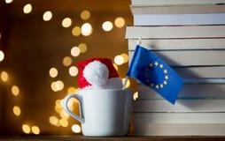 白色杯子和圣诞节帽子有欧洲联盟标志的 库存照片