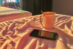 白色杯子和黑智能手机在床上在晴朗的晚上从开放阳台门点燃 夏天在热带 概念家庭舒适 免版税库存图片