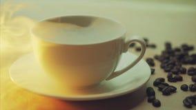白色杯子在咖啡豆背景的通入蒸汽的热的饮料  免版税库存照片