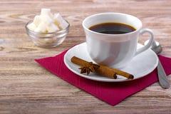 白色杯子在茶碟的黑热的咖啡,供食与在一根碗、茶匙子、茴香和肉桂条的白糖立方体在木t 免版税图库摄影