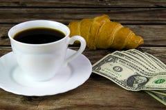 白色杯子无奶咖啡、新月形面包和美元 免版税库存图片