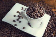 白色杯子有很多咖啡豆 库存图片