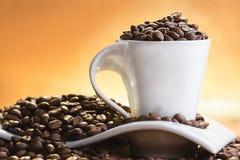 白色杯子有很多咖啡豆 免版税库存图片