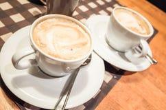白色杯子有很多热奶咖啡在木桌上站立 免版税库存照片