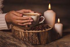 白色杯子用咖啡在女孩、蜡烛、毛皮和咖啡豆的手上 库存图片