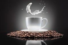 白色杯子用咖啡豆和牛奶飞溅 库存照片