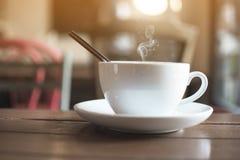 白色杯子用在桌上的通入蒸汽的热的咖啡有在咖啡馆的bokeh背景 免版税库存照片