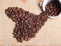白色杯子用在粗麻布背景的咖啡豆 库存照片