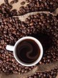 白色杯子用在粗麻布背景的咖啡 库存图片