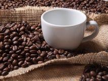 白色杯子用在粗麻布背景的咖啡 库存照片