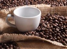 白色杯子用在粗麻布背景的咖啡 免版税库存照片
