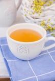 白色杯子用在蓝色餐巾,与花的柳条筐,投手,白色台式的清凉茶 库存照片