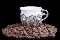 白色杯子用在黑背景的咖啡豆 免版税库存图片