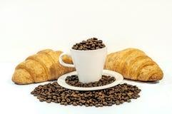 白色杯子用新鲜的咖啡豆和两法国人新月形面包 免版税库存图片
