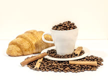 白色杯子用新鲜的咖啡豆和法国新月形面包 免版税库存图片