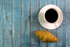 白色杯子用无奶咖啡和新月形面包在蓝色木背景 库存照片