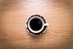 白色杯子用站立在木桌上的棕色,烤豆的黑,热的咖啡 免版税库存图片