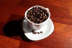 白色杯子用里面咖啡豆 免版税库存图片