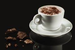 白色杯子的特写镜头图象有很多拿铁咖啡在黑暗的背景 免版税图库摄影