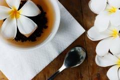 白色杯子锡兰茶和黄色异乎寻常的花羽毛-与木老桌的平的位置斯里兰卡` s背景 免版税图库摄影