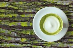 白色杯子matcha绿茶与泡沫的拿铁艺术在土气与拷贝空间的青苔木桌上 库存照片