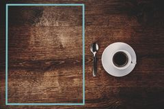 白色杯顶视图用在一个白色茶碟和茶匙的无奶咖啡在与蓝色框架的黑褐色木背景在左边 免版税库存照片