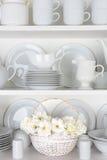 白色板材在有玫瑰的碗柜 免版税图库摄影