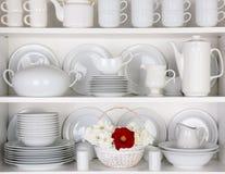 白色板材在有玫瑰篮子的碗柜  免版税库存图片