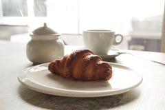 白色板材用与杯子的新月形面包新鲜的无奶咖啡 图库摄影