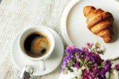 白色板材用与杯子的新月形面包新鲜的无奶咖啡 免版税库存照片