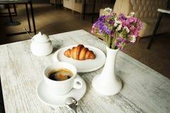 白色板材用与杯子的新月形面包新鲜的无奶咖啡 免版税图库摄影