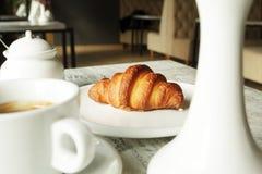 白色板材用与杯子的新月形面包新鲜的无奶咖啡 库存照片