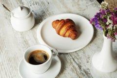 白色板材用与杯子的新月形面包新鲜的无奶咖啡 免版税库存图片
