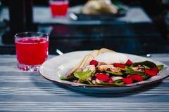 白色板材用在沙拉的荷包蛋与刀子和叉子 下块玻璃用红色汁液 在背景的蓝色桌布 图库摄影
