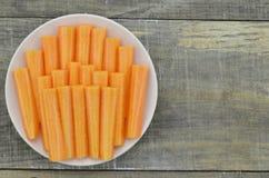 白色板材用红萝卜裁减棍子在木背景的 库存图片