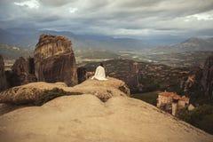 白色格子花呢披肩的单独女性在迈泰奥拉修道院的岩石神色边缘  岩石和修道院的女性  免版税库存照片