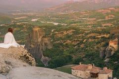 白色格子花呢披肩的单独女性在迈泰奥拉修道院的岩石神色边缘  岩石和修道院的女性  库存图片
