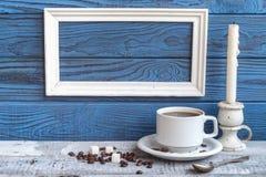 白色框架、咖啡杯和一candel在蓝色蟒蛇背景  库存照片