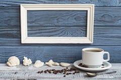 白色框架、咖啡杯和壳在蓝色委员会背景  免版税库存照片