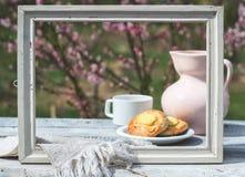 白色框架、瓷桃红色水罐、杯子和面包店在白板桌上以开花的灌木为背景 库存照片