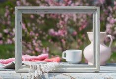 白色框架、瓷桃红色水罐、杯子和餐巾在白板桌上以开花的灌木为背景 免版税库存照片
