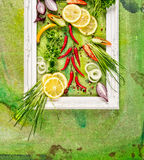 白色框架用新鲜的香料、辣椒、庭院草本和柠檬在绿色背景,顶视图 库存图片