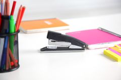 白色桌面特写镜头有笔记薄、笔、咖啡杯和其他项目的 选择聚焦 图库摄影