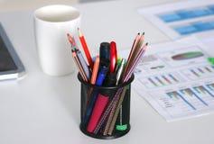白色桌面特写镜头有笔记薄、笔、咖啡杯和其他项目的 选择聚焦 库存照片