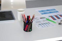 白色桌面特写镜头有笔记薄、笔、咖啡杯和其他项目的 选择聚焦 库存图片