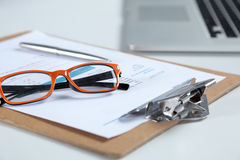 白色桌面特写镜头有膝上型计算机、玻璃、咖啡杯、笔记薄和其他项目的在模糊的城市背景 免版税库存图片