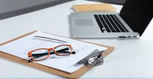 白色桌面特写镜头有膝上型计算机、玻璃、咖啡杯、笔记薄和其他项目的在模糊的城市背景 免版税库存照片
